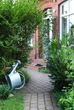 Close up from a paved path with house facade and watering can. Stock Photography