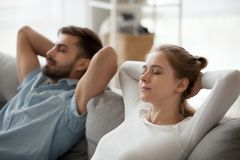 Close up of mindful couple relaxing on sofa at home stock photography