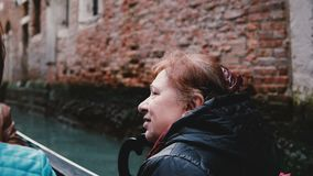 Close-up of peaceful senior Caucasian woman enjoying atmospheric gondola excursion tour on famous Venice canals, Italy. Active older happy female tourist stock video