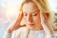 Close up of peaceful woman with closed eyes. Contemplation. Close up of pleasant woman being thoughtful while touching her temples with fingers and keeping her stock image