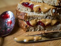 Peanut Butter and Jelly Sandwich on Cutting Board, Knife and Spoon. A close up of a peanut butter and jelly sandwich, cut in half and stacked, on a wooden stock photo