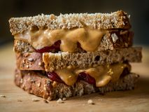 Peanut Butter and Jelly Sandwich on Cutting Board, Close Up Profile, Cut in Half. A close up of a peanut butter and jelly sandwich, cut in half and stacked, on a stock photo