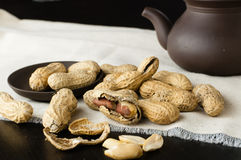 Close up peanuts. On a small plate and linen tablecloth with clay teapot stock photography