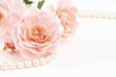 Close up of pearls and pink roses. Close up of pastel pink roses with string of pearls. Muted dusty colors with copy space Stock Photos