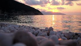 Close-up pebble stones beach at sunset over sea. stock video footage