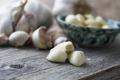 Peeled Garlic Cloves. Close up of peeled garlic cloves with garlic head and unpeeled cloves in background Stock Photography