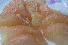 Peeled pomelo fruit on dish. Royalty Free Stock Photo