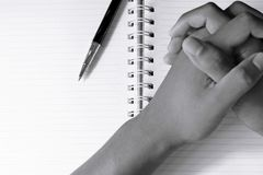Close up of pen and blur man`s hands in spiral notepad. Black and white tone Stock Photo