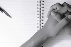 Close up of pen and blur man`s hands in spiral notepad. Black and white tone Stock Photos