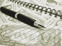 Close up of Pen on Notebook with blurred American Dollar in Back Stock Image