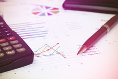 Close up pen is on summary report and calculator on table office Stock Image