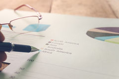 Close up pen with summary report and eyeglasses on table office. Royalty Free Stock Image
