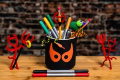 Close up of a pencil cup with spooky halloween eyes surrounded by Pipe Cleaner Devils and other scary objects.  Some Negative