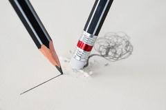 Close up of a pencil eraser removing a crooked line and the close up of a sharpened pencil writing a straight line. stock photo