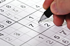 Close-up a pencil in hand and puzzle Sudoku. Stock Image