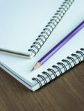 Close up pencil and spiral notebook on wood table Royalty Free Stock Photos