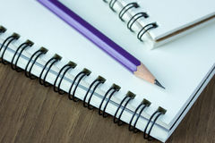 Close up pencil and spiral notebook on wood table Stock Photos