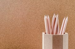 Close up of pencils in wooden holder with brown background Stock Photo