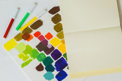 Close-up of pens of different bright colors, multicolored stains of colors on light background of paper texture, top stock photography