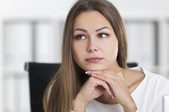 Close up of pensive blond woman in white in office Stock Image