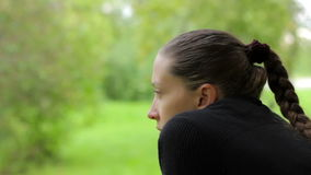 Close-up of a pensive girl with a dreamy look on the background of green foliage stock video