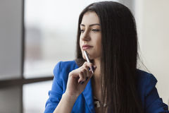 Close up of pensive young businesswoman with pen Stock Images