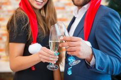 Close-up people with champagne on a blurred background. Man and woman on a Christmas party concept. Close-up picture of festive men and women cheering and Royalty Free Stock Photography