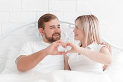 Love, people and the concept of happiness - smiling couple in bed, hands making a heart shape. Royalty Free Stock Image