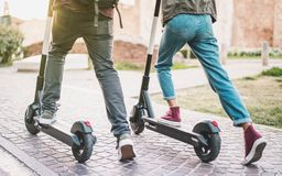 Close up of people couple using electric scooter in city park - Millenial students riding new modern ecological mean of transport