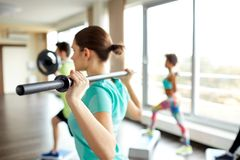 Close up of people exercising with bars in gym Stock Image