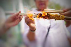 Close up people hands holding incense sticks by the fire. Bangkok, Thailand - February 2,2015 : Close up people hands holding incense sticks by the fire of Stock Images