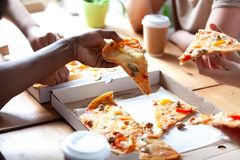 Close up people hands holds pieces of pizza stock photography