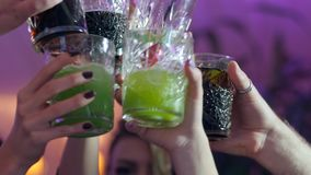 Close-up of people hands make toast with glasses with alcoholic multi-colored cocktails at club stock video