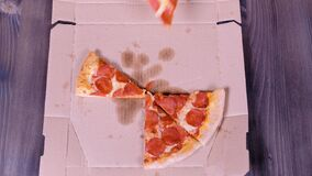 Close-up of people hands taking slices pizza from food delivery open box.