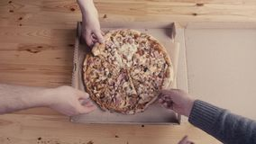 Close-up Of People Hands Taking Slices Pizza from food delivery open box. Tasty Service to office