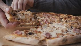 Close-up Of People Hands Taking Slices Pizza from food delivery open box. Tasty Service to office stock video footage