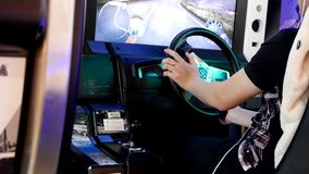 Close up people having fun and playing racing video game. Inside Buranby shopping mall stock video footage