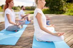 Close up of people making yoga exercises outdoors Royalty Free Stock Photography