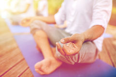 Close up of people making yoga exercises outdoors Stock Photos