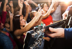 Close up of people at music concert in night club. Holidays, music, nightlife and people concept - close up of musiciab playing electric guitar on stage over Stock Images