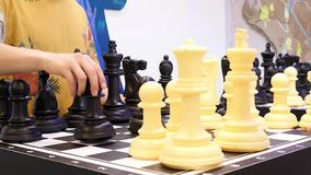 Close up for people playing giant chess, board games concept. Media. Two classmates play big chess at a science activity