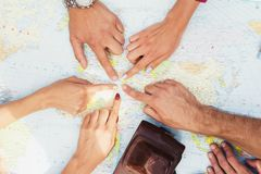 Close up. People point a finger at a place on a paper map. Next to it is a vintage photo camera. Close up. People point a finger at a place on a paper map. Next Stock Photo
