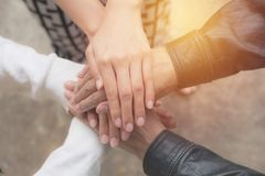Close up of people putting their hands together. Stack of hands stock photos