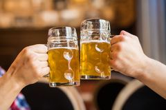 Close-up of people toasts with beer in pub. Beer cheers Royalty Free Stock Photos