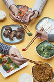 Close up of people using chopsticks with Chinese food Royalty Free Stock Photography