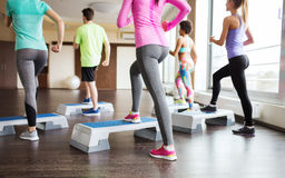 Close up of people working out with steppers in gym Royalty Free Stock Photos