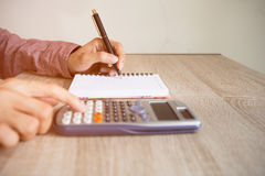 Close up people with writing in a notebook. Close up people with calculator counting making notes on table, hand is writing in a notebook. Concept savings Royalty Free Stock Photos