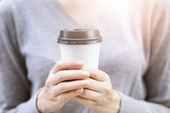 Close up people young female hand holding paper cup of take away drinking coffee on natural morning sunlight. stock image
