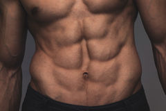 Close up perfect abs. Sexy muscular male torso six packs. Handsome shirtless muscular young man Stock Photography