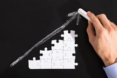 Person Arranging Puzzles On Blackboard. Close-up Of A Person Arranging White Puzzles Against Upward Arrow On Blackboard Royalty Free Stock Photography